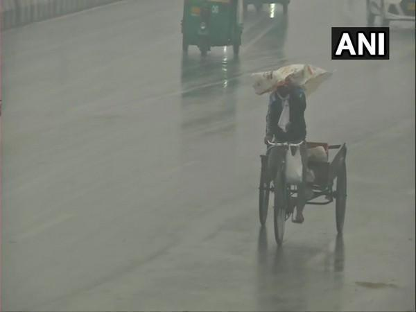 A rickshaw puller at the Ghazipur border covers his head to protect himself from the light showers. (Photo/ANI)