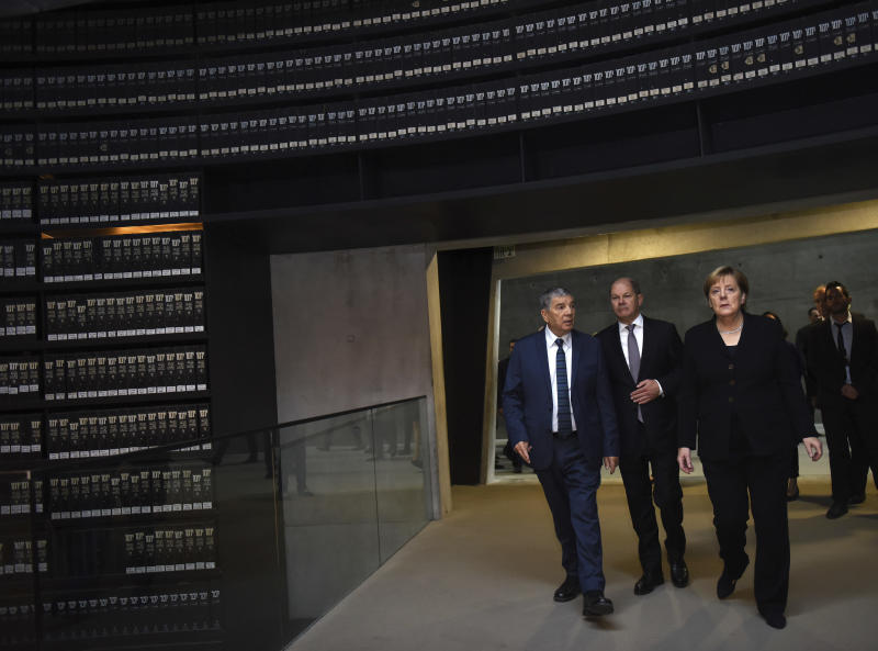 German Chancellor Angela Merkel, right, enters the Hall of Names in the Yad Vashem Holocaust Museum in Jerusalem, Israel, Thursday Oct. 4, 2018. (Debbie Hill/Pool via AP)