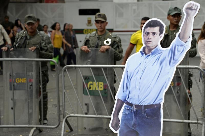 A poster of arrested opposition leader Leopoldo Lopez stands next to a military cordon guarding the Venezuelan courthouse in Caracas on July 23, 2014
