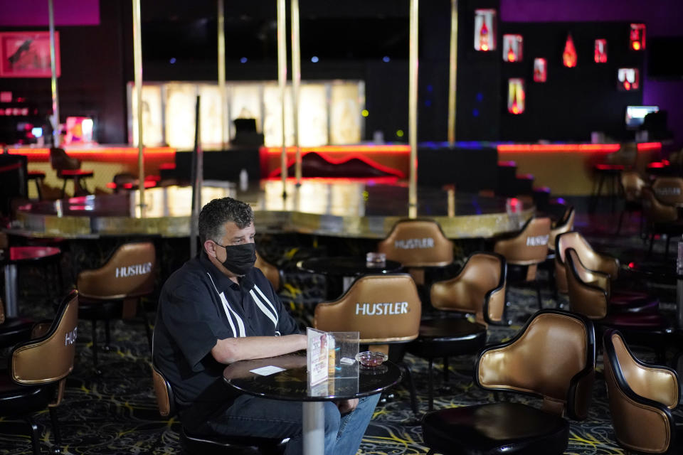 Jeff Cantrell waits at Larry Flint's Hustler Club strip club after getting his second dose of coronavirus vaccine Friday, May 21, 2021, in Las Vegas. Las Vegas officials held a pop-up vaccine clinic at the strip club (AP Photo/John Locher)