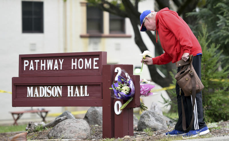Resident Tom Parkinson places flowers on a sign at the Veterans Home of California, the morning after a hostage situation in Yountville, Calif., on Saturday, March 10, 2018. A daylong siege at The Pathway Home ended Friday evening with the discovery of four bodies, including the gunman, identified as Albert Wong, a former Army rifleman who served a year in Afghanistan in 2011-2012. (AP Photo/Josh Edelson)