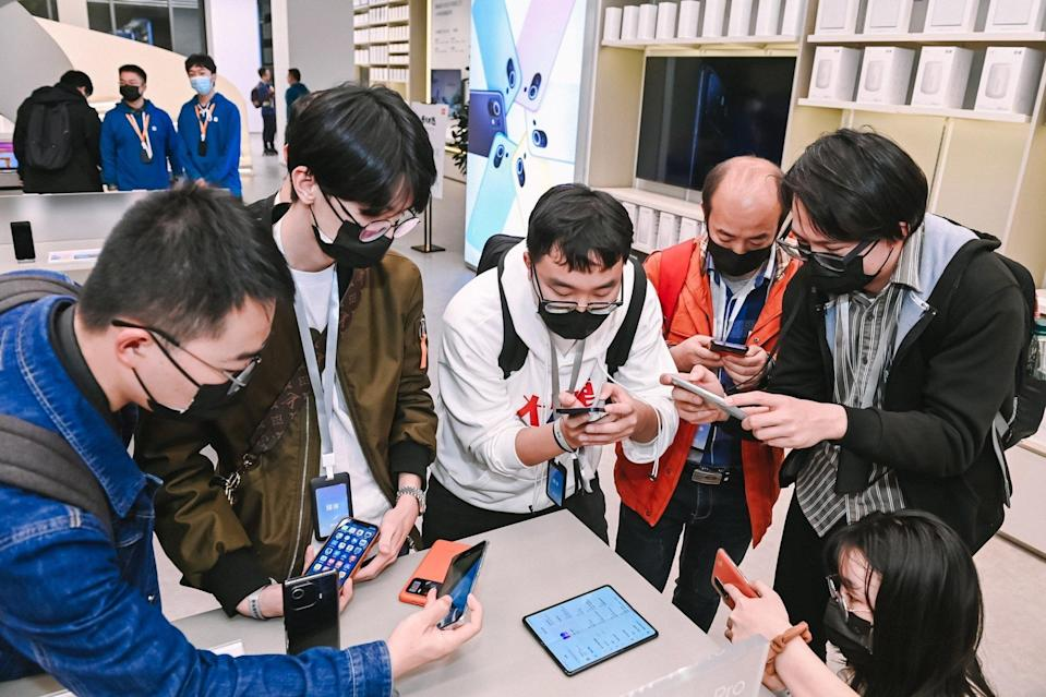 People look at Xiaomi's new foldable smartphone, the Mi Mix Fold, during a product unveiling event in Beijing, China, on March 30, 2021. Photo: Handout