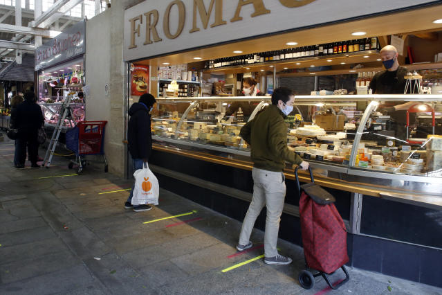 People wearing face masks to shop in an indoor food market in in Paris. (Thibault Camus/AP)