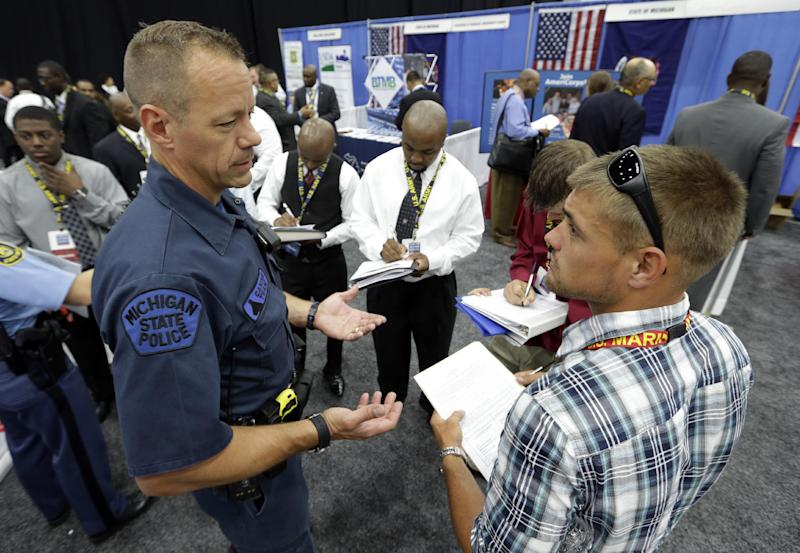 Michigan State Police Trooper Matt McCaul, left, talks with military veteran Christopher Honold, of Canton, Mich., in Detroit, Tuesday, June 26, 2012 . Thousands of veterans are in Detroit this week for job fair, open house, small business conference. (AP Photo/Paul SancyaT)