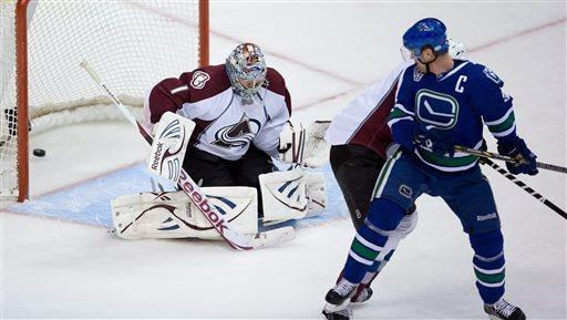 Colorado Avalanche goalie Semyon Varlamov, left, of Russia, allows a goal to Vancouver Canucks' Daniel Sedin, of Sweden, unseen, as his Henrik Sedin, of Sweden, watches during the third period of an NHL hockey game in Vancouver, British Columbia, on Thursday, March 28, 2013. (AP Photo/The Canadian Press, Darryl Dyck)