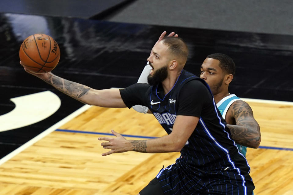 Orlando Magic guard Evan Fournier (10) gets off a shot in front of Charlotte Hornets forward P.J. Washington during the first half of an NBA basketball game, Monday, Jan. 25, 2021, in Orlando, Fla. (AP Photo/John Raoux)