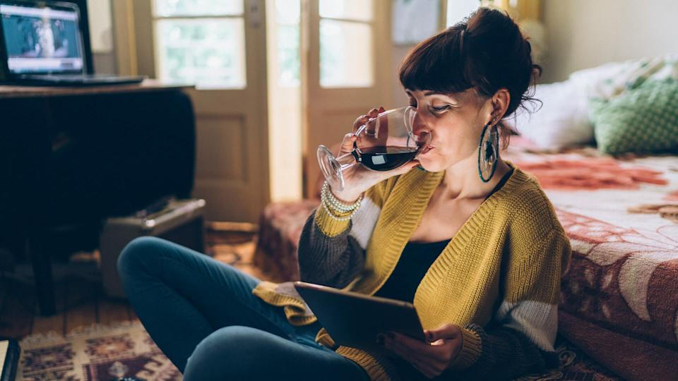 Young woman at home drinking red wine and using tablet.