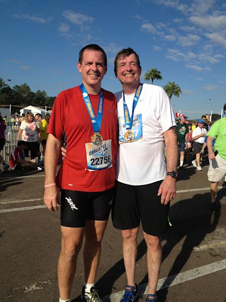 """In this Jan. 12, 2013 photo provided by the family, Doug Olson, right, and his son, Jon, stand together after running a half-marathon in Orlando, Fla. As of December 2013, Doug Olson, 67, a scientist for a medical device maker, shows no sign of cancer since gene therapy in September 2010 for chronic lymphocytic leukemia he had had since 1996. """"Within one month he was in complete remission. That was just completely unexpected. He probably had about 4 pounds of tumor that was eradicated in 30 days,"""" said Porter, his doctor at U Penn. (AP Photo/Margit Olson)"""