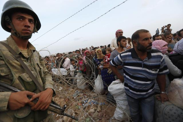 A Turkish soldier stands guard as Syrian Kurdish refugees wait behind the border fences to cross into Turkey near the southeastern town of Suruc in Sanliurfa province September 27, 2014. Turkish troops could be used to help set up a secure zone in Syria, if there was an international agreement to establish such a haven for refugees fleeing Islamic State fighters, President Tayyip Erdogan said in comments published on Saturday. Militants still held their positions around 10 kilometres west of Kobane inside Syria, the Reuters witness said, with Kurdish positions the last line of defence between the fighters and the town. Kobane sits on a road linking north and northwestern Syria and Kurdish control of the town has prevented Islamic State fighters from consolidating their gains, although their advance has caused more than 150,000 Kurds to flee to Turkey since last week. REUTERS/Murad Sezer (TURKEY - Tags: POLITICS CIVIL UNREST CONFLICT SOCIETY IMMIGRATION MILITARY TPX IMAGES OF THE DAY)