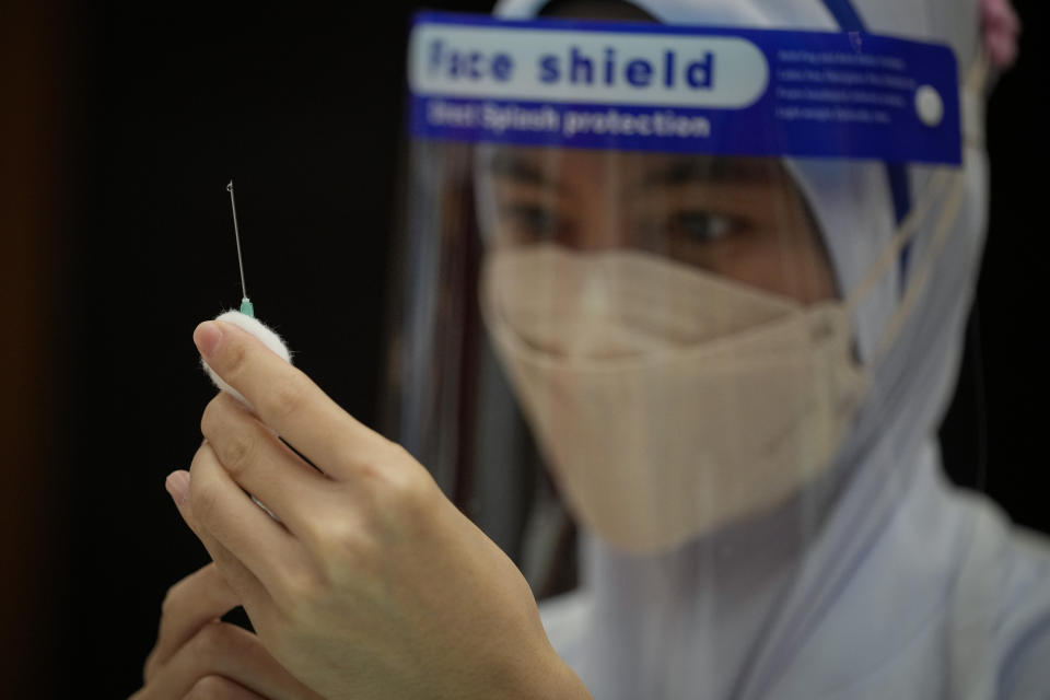 A Nurse prepares a dose of the Pfizer vaccine against the coronavirus disease (COVID-19) for a secondary school student at a vaccine center in Shah Alam, Malaysia, Monday, Sept. 20, 2021. (AP Photo/Vincent Thian)