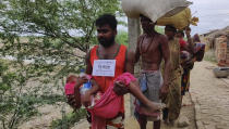A disaster management volunteer carries a sick child as villagers on the Bay of Bengal coast are evacuated as a precaution against Cyclone Amphan at Bakkhali, South 24 Parganas, West Bengal, India, Tuesday, May 19, 2020. The powerful cyclone was moving toward India and Bangladesh on Tuesday as authorities tried to evacuate millions of people while maintaining social distancing. (AP Photo/Mehaboob Gazi)
