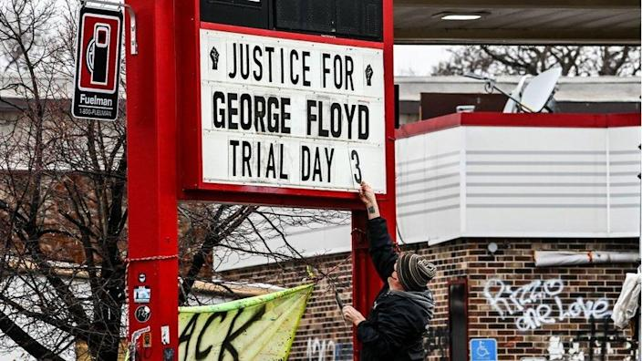 A man changes the number of a sign board at a makeshift memorial of George Floyd before the third day of jury selection begins in the trial of former Minneapolis Police officer Derek Chauvin