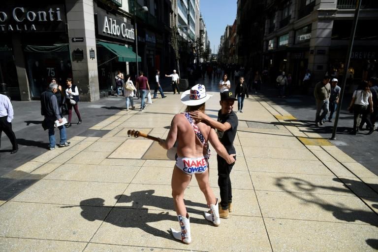 Robert John Burck, an American street performer known as the Naked Cowboy, poses with a young fan during a visit to Madero street in Mexico City
