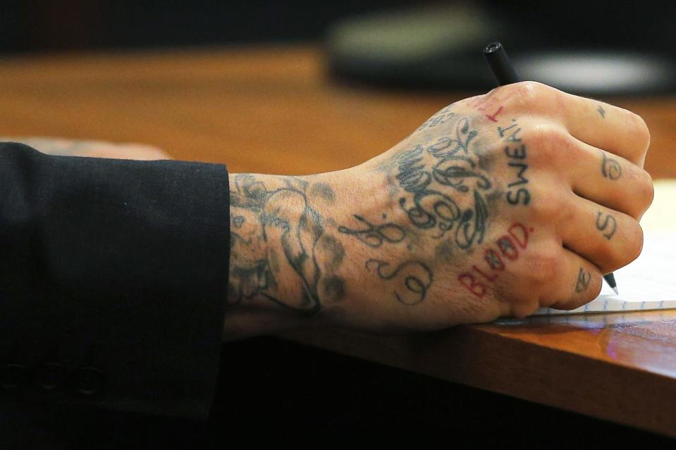 Former New England Patriots tight end Aaron Hernandez writes a note during his murder trial at Bristol County Superior Court in Fall River, Massachusetts February 4, 2015. Hernandez is accused of murdering semi-professional football player Odin Lloyd. REUTERS/Brian Snyder (UNITED STATES - Tags: CRIME LAW SPORT FOOTBALL)