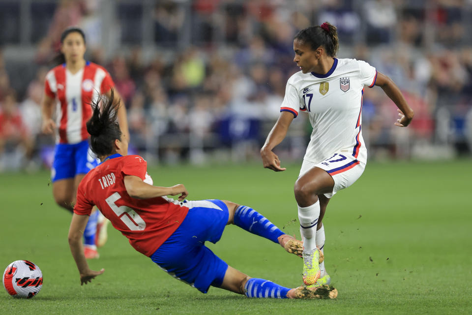 United States midfielder Catarina Macario, right, passes the ball against Paraguay defender Tania Riso (5) during the first half of an international friendly soccer match, Tuesday, Sept. 21, 2021, in Cincinnati. (AP Photo/Aaron Doster)