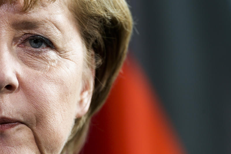 FILE - In this April 17, 2013 file photo German Chancellor Angela Merkel stands in front of a German national flag as she attends a news conference with the Prime Minister of Estonia Andrus Ansip after a meeting at the chancellery in Berlin. (AP Photo/Markus Schreiber, file)