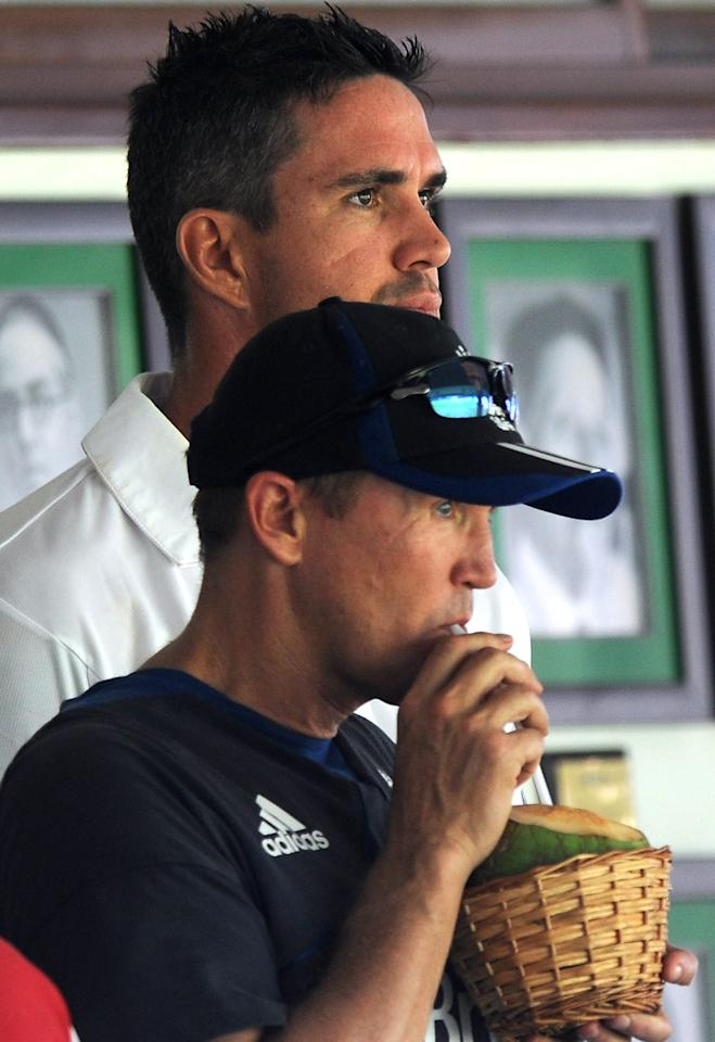 MUMBAI, INDIA - OCTOBER 31:  Kevin Pietersen of England and Andy Flower team Director (front) look on outside the dressing room as the later enjoys a drink during the second day of the first practice match between England and India A at the CCI (Cricket Club of India) ground,  on October 31, 2012 in Mumbai, India.  England will play three practice matches before the start of four test series  (Photo by Pal Pillai/Getty Images)