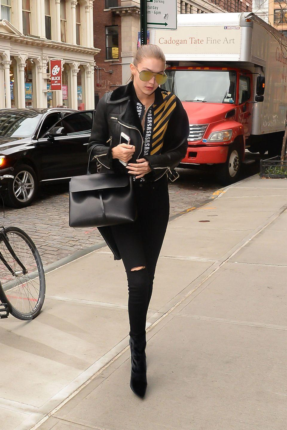<p>In a leather shearling jacket, striped zip-up top, black skinny jeans, velvet ankle boots, Mansur Gavriel bag and reflective aviators while out in NYC.</p>