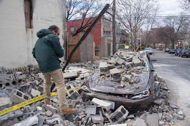 <p>An insurance company employee checks the damage to a car after a partially burnt building collapsed due to strong winds in Northeast Washington on March 2, 2018. (Photo: Nicholas Kamm/AFP/Getty Images) </p>