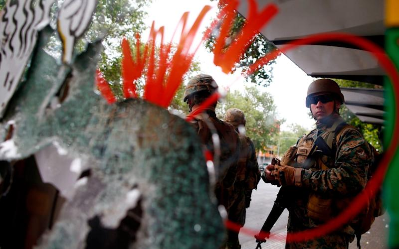 Chilean army soldiers dispatched to protect a mall ransacked by protesters in Santiago - AFP