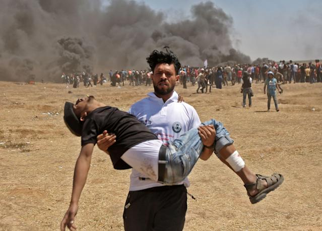 <p>A Palestinian carries an injured protester during clashes with Israeli forces near the border between the Gaza Strip and Israel on May 14, 2018, during a demonstration on the day of the U.S. Embassy move to Jerusalem. (Photo: Mahmud Hams/AFP/Getty Images) </p>