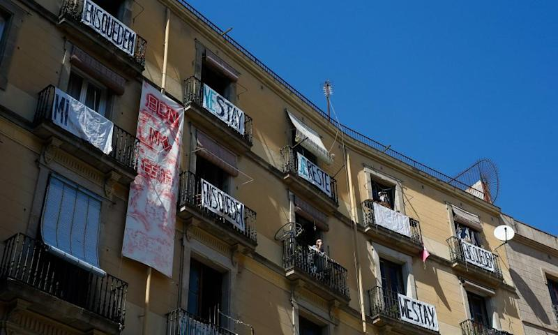 Signs reading 'stay at home' hung from balconies in Barcelona