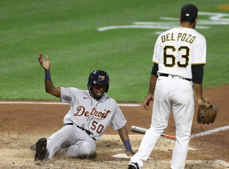 Tigers pinch runner Travis Demeritte slides across home plate to score a run as Pirates pitcher Miguel Del Pozo looks on during the seventh inning of the Tigers' 17-13 win in extra innings on Friday, Aug. 7, 2020, in Pittsburgh.