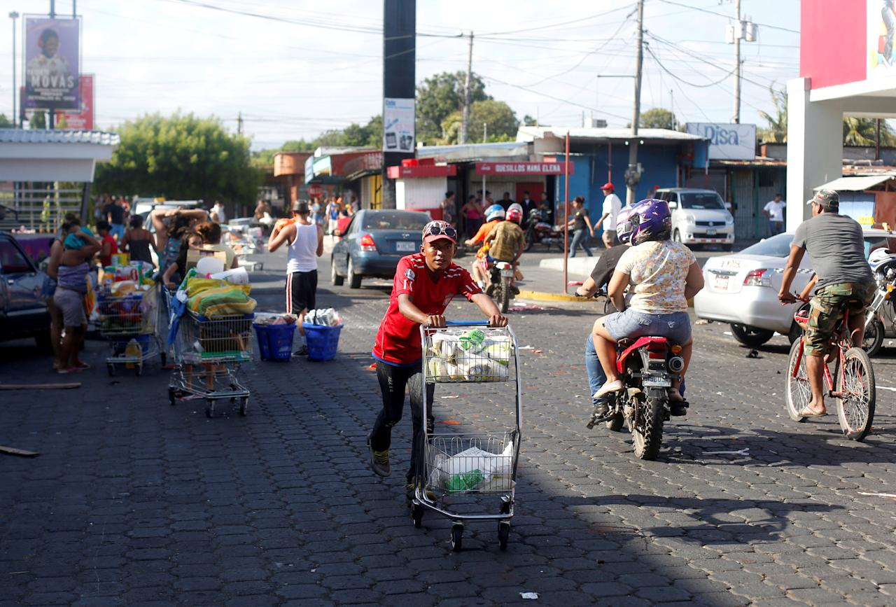 People with goods looted from a store walk pushing a shopping trolley along a street after a protest over a controversial reform to the pension plans of the Nicaraguan Social Security Institute (INSS) in Managua, Nicaragua April 22, 2018. REUTERS/Jorge Cabrera