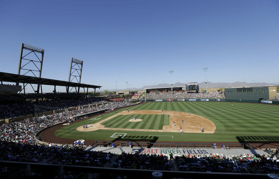 FILE - In this March 18, 2016, file photo, fans at Salt River Fields at Talking Stick watch a spring training baseball game between the Arizona Diamondbacks and the Los Angeles Dodgers in Scottsdale, Ariz. The Diamondbacks sold out their entire spring allotment of tickets in less than 24 hours after they went on sale to the public. Approximately 2,200 tickets were sold for all 14 of the team's home games, with fans spread throughout the park in pods of two, four or six seats and masks are required except when eating or drinking. (AP Photo/Jeff Chiu, File)