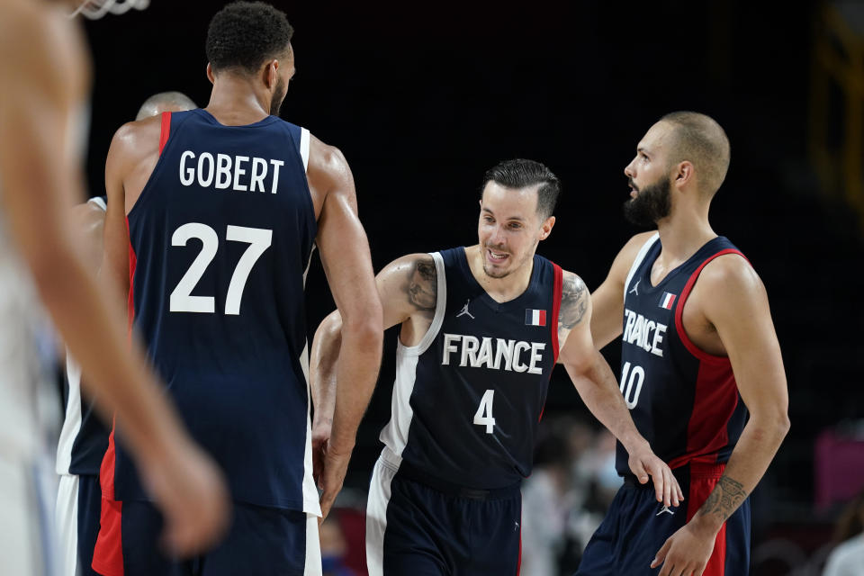 France's Thomas Heurtel (4) celebrates with teammates Rudy Gobert (27) and Evan Fournier (10) at the end of a men's basketball quarterfinal round game against Italy at the 2020 Summer Olympics, Tuesday, Aug. 3, 2021, in Saitama, Japan. (AP Photo/Charlie Neibergall)