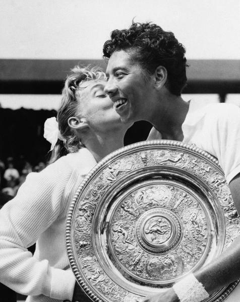 FILE - In this July 6, 1957 file photo, Althea Gibson, of New York City, holds the women's singles tennis trophy at Wimbledon, England, while being kissed by her finals opponent, Darlene Hard, of Montebello, Calif. Gibson, who became the first African-American to win a Wimbledon championship, was among the more than a million black people who weren't counted in the 1940 census. There is no record of Gibson and her family in the decennial census, the records of which were released online to the public by the U.S. Census Bureau on April 2 after a 72-year confidentiality period lapsed. (AP Photo, File)