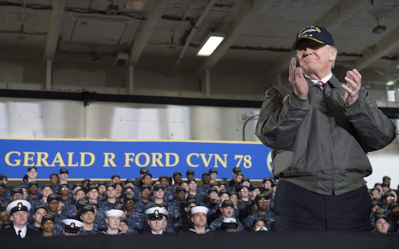 US President Donald Trump applauds aboard the pre-commissioned USS Gerald R. Ford aircraft carrier in Newport News, Virginia - Credit: AFP
