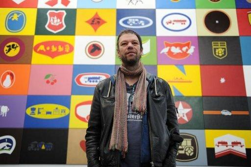 "German artist Konstantin Voit poses for a picture in front of his installation ""Die Malfabrik: Werbeblock"""
