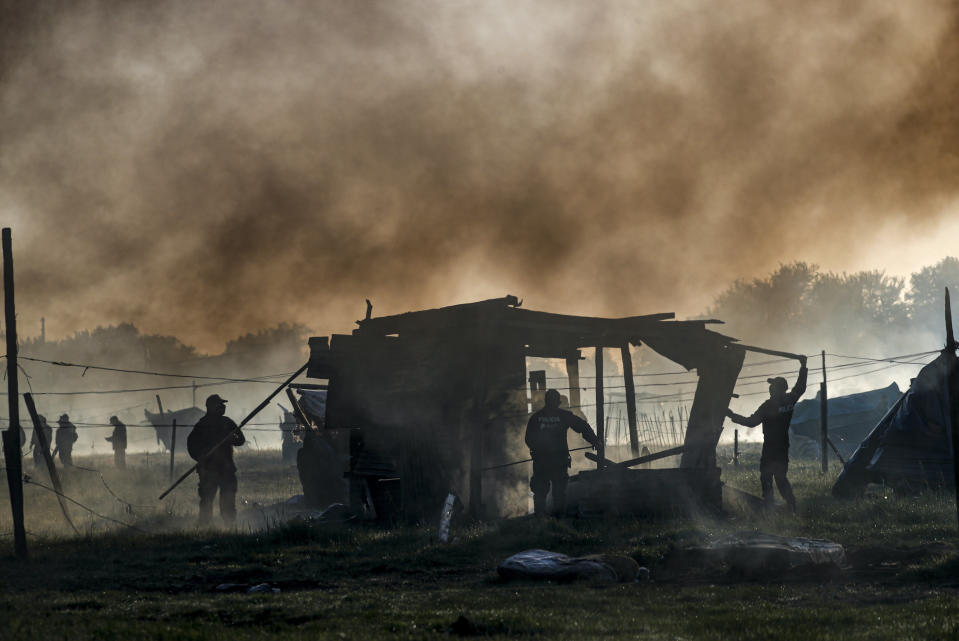 Police destroy shack homes as they carry out the eviction of a squatters camp in Guernica, Buenos Aires province, Argentina, Thursday, Oct. 29, 2020. A court ordered the eviction of families who are squatting here since July, but the families say they have nowhere to go amid the COVID-19 pandemic. (AP Photo/Natacha Pisarenko)