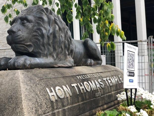A sign with a QR code is paired with the Thomas Temple Fountain located beside the Beaverbrook Art Gallery. (Gary Moore/CBC - image credit)
