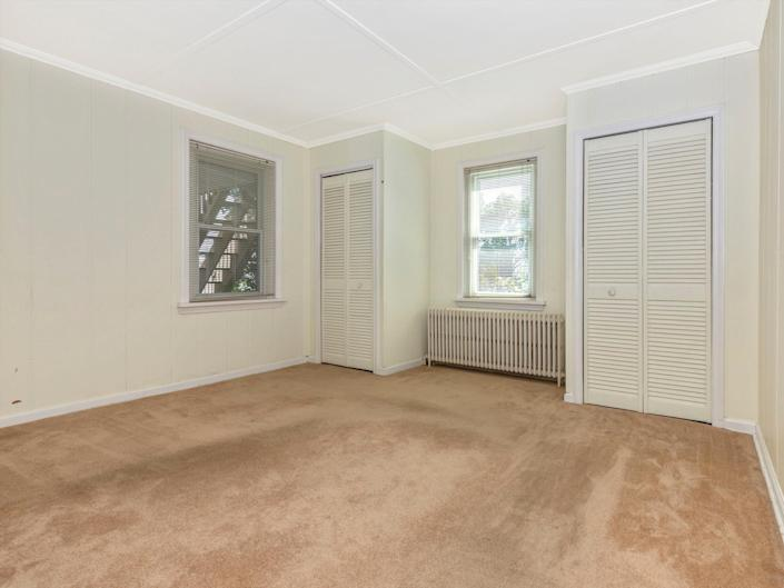 an empty bedroom with a carpet and two windows