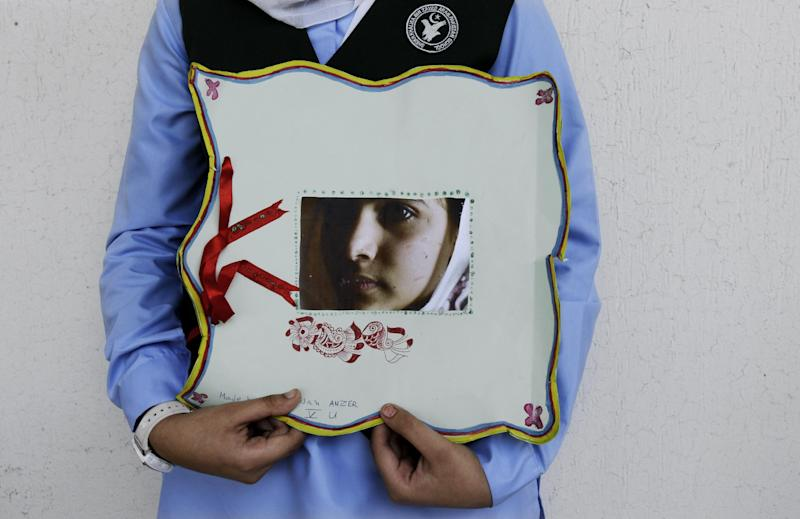 A Pakistani student holds a picture of 14-year-old schoolgirl Malala Yousufzai, who was shot last Tuesday by the Taliban for speaking out in support of education for women, during a tribute at the Pakistani Embassy in Abu Dhabi, United Arab Emirates, Monday, Oct. 15, 2012. Pakistan airlifted a 14-year-old activist who was shot and seriously wounded by the Taliban to the United Kingdom for treatment Monday, a move that will give her access to the specialized medical care she needs to recover and also protect her from follow-up attacks threatened by the militants. (AP Photo/Kamran Jebreili)