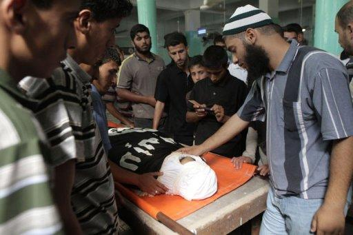 """Relatives and friends mourn over the body of 21-year-old Ghaleb Ermilat during his funeral in Rafah. Ermilat was named a """"global jihad"""" operative by the Israeli military, who say he put together a deadly ambush on Israel's border with Egypt"""