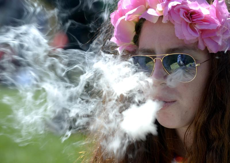 A woman smokes marijuana during the 4/20 Rally at the Civic Center in Denver