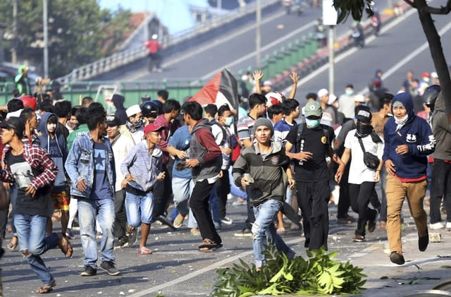 Protesters run during a clash with police