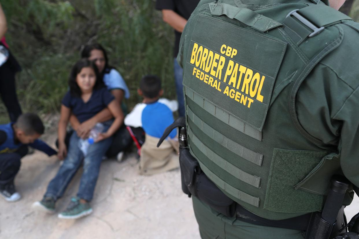 A Central American family waits to be taken into custody on June 12, 2018, near McAllen, Texas.