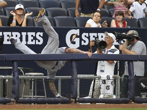 Toronto Blue Jays third baseman Brett Lawrie falls into a photo well while diving for a foul ball during the third inning of the baseball game against the New York Yankees Wednesday, July 18, 2012 at Yankee Stadium in New York. Lawrie did not make the catch. (AP Photo/Seth Wenig)