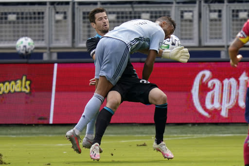 Sporting Kansas City forward Khiry Shelton (11) collides with FC Dallas goalkeeper Jimmy Maurer during the first half of an MLS soccer match in Kansas City, Kan., Saturday, Sept. 19, 2020. (AP Photo/Orlin Wagner)