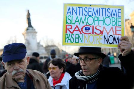 "People attend a national gathering to protest antisemitism and the rise of anti-Semitic attacks in the Place de la Republique in Paris, France, February 19, 2019. The writing on the sign reads: ""Antisemitism, islamophobia, racism - not in our name"".  REUTERS/Gonzalo Fuentes"