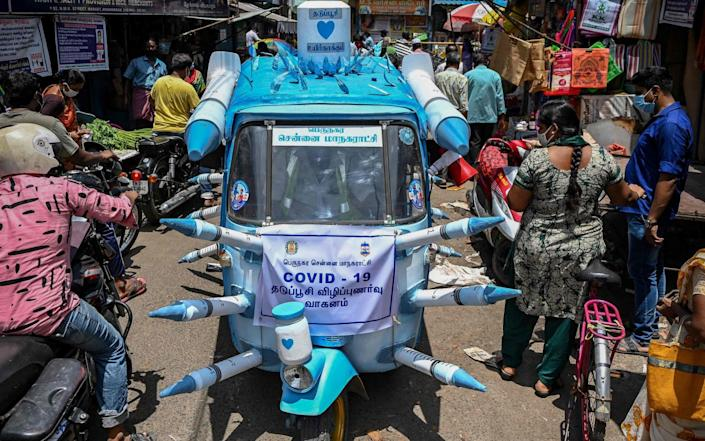 A municipal worker drives an auto-rickshaw decorated with mock syringes through the streets to boost awareness amid people on the importance of Covid-19 vaccines in Chennai - ARUN SANKAR