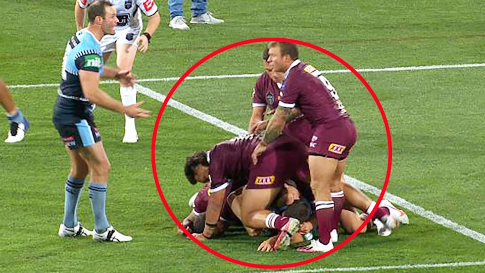 Queensland players, pictured here laying on the tackle in the dying stages of the State of Origin opener.