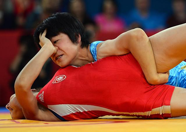 LONDON, ENGLAND - AUGUST 08: Hitomi Obara of Japan (blue) competes against Maroi Mezien of Tunesia (red) in the Women's Freestyle 48 kg Wrestling on Day 12 of the London 2012 Olympic Games at ExCeL on August 8, 2012 in London, England. (Photo by Lars Baron/Getty Images)