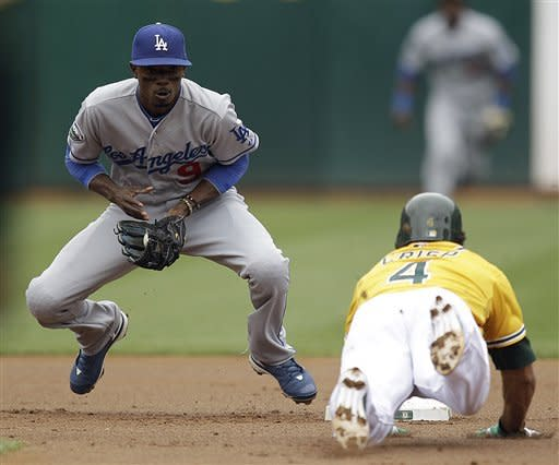 Los Angeles Dodgers shortstop Dee Gordon, left, prepares to make the tag on Oakland Athletics' Coco Crisp during the first inning of a baseball game, Thursday, June 21, 2012, in Oakland, Calif. Crisp was tagged out while attempting to steal second. (AP Photo/Ben Margot)