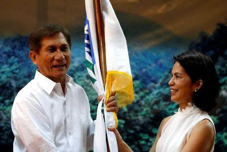 FILE PHOTO: Newly appointed Environment Minister Roy Cimatu holds the Department of Environment flag from his predecessor  environmentalist Regina Lopez, during a turn over ceremony in Quezon City Metro Manila