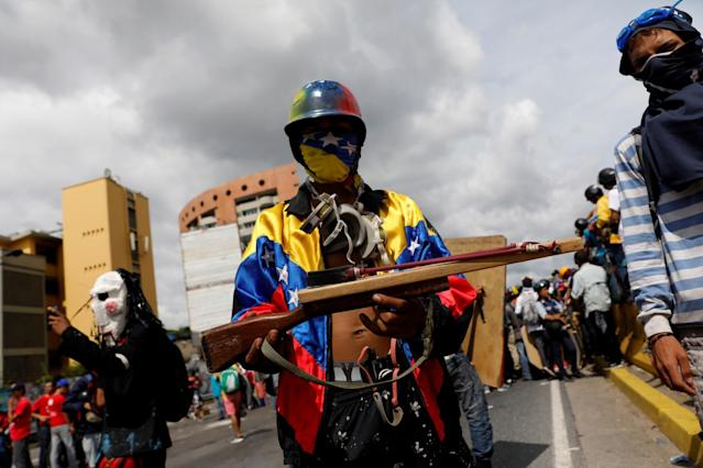 <p>An opposition supporter shows a sling shot built to resemble a gun during a rally against President Nicolas Maduro in Caracas, Venezuela, May 15, 2017. (Carlos Garcia Rawlins/Reuters) </p>